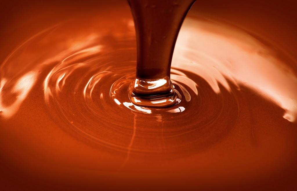 Chocolate flow. Close up of liquid hot chocolate pouring closeup. Chocolate swirl