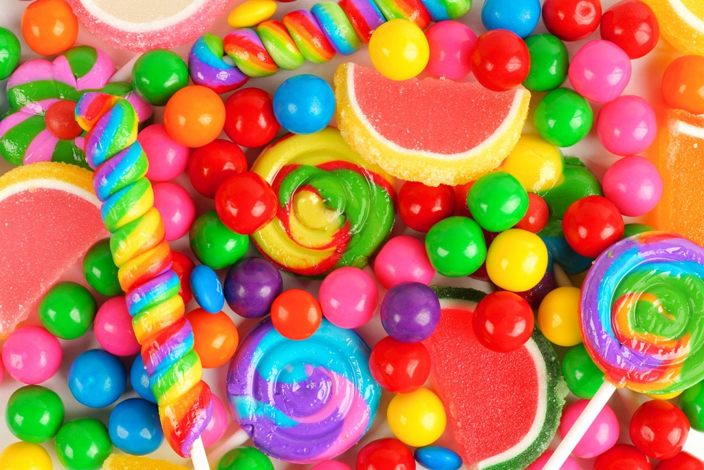 Colorful background of assorted candies including gum balls lollipops and jelly candies