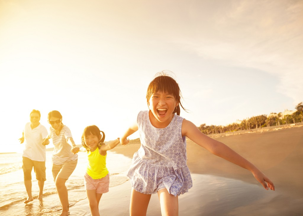 happy  asian family running on the beach